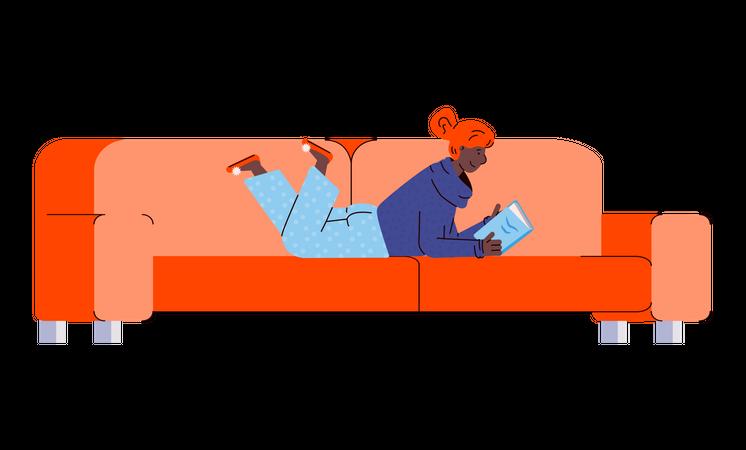 Cartoon woman reading a book lying on her stomach on orange sofa Illustration